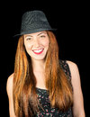 Happy smiling young woman with long red hair and hazel eyes wear wearing a pinstriped fedora isoaled on black Royalty Free Stock Images
