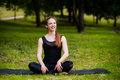 Happy, smiling, young woman resting on the grass at the park after the yoga. She is wearing dark leggings. Royalty Free Stock Photo