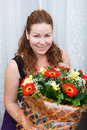 Happy smiling young woman sitting with flowers Stock Photography