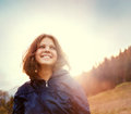 Happy smiling young woman in sunset light on the mountain hill Royalty Free Stock Photo