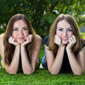 Happy smiling young women lying on grass against background of summer green park Stock Image