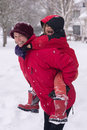 Happy snow a laughing mother carries her small son piggyback through falling as he happily catches flakes on his tongue Royalty Free Stock Photos