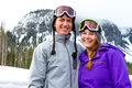 Happy snowboarding couple a together on the mountain resort in the snow for a day of skiing and Stock Image