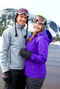 Happy snowboarding couple a together on the mountain resort in the snow for a day of skiing and Stock Photography