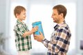 Happy son gives his father gift fathers day family holiday vacation Stock Photography