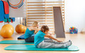 Happy sports family mother and son perform gymnastic exercises Royalty Free Stock Photos