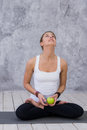 Happy sports woman holding apple sitting on a yoga mat over gray background
