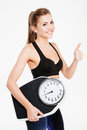 Happy sportswoman holding weight scales and showing thumbs up gesture Royalty Free Stock Photo