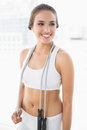 Happy sporty brunette wearing a skipping rope around the neck in bright room Stock Photos