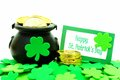 Happy st patricks day card with pot of gold and shamrocks over white Stock Photography