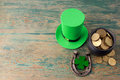 Happy St Patricks Day leprechaun hat with gold coins and lucky charms on vintage style green wood background. Top view Royalty Free Stock Photo