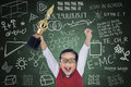 Happy student boy hold trophy in class shouting while holding a classroom Royalty Free Stock Image