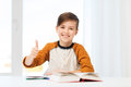 Happy student boy with textbook showing thumbs up education childhood people and school concept and notebook at home Stock Images