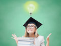 Happy student girl in bachelor cap with books Royalty Free Stock Photo