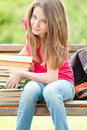 Happy student girl  on bench with pile of books Royalty Free Stock Photography