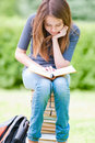 Happy student girl sitting on pile of books Royalty Free Stock Photo