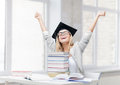 Happy student in graduation cap with stack of books Royalty Free Stock Photography