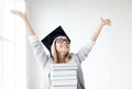Happy student in graduation cap with stack of books Royalty Free Stock Images