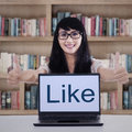 Happy student showing like button on laptop Royalty Free Stock Photo