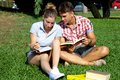 Happy students with books in park good looking models sitting on green grass studying smiling Stock Photography