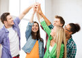 Happy students giving high five at school education and friendship concept Stock Images