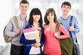 Happy students group of young teenager standing and smiling with books and bags Stock Photo