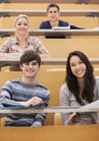 Happy students sitting in a lecture hall amused while having the books open Stock Image