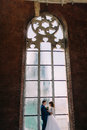 Happy stylish bride and groom holding each other in front of arched window old gothic cathedral Royalty Free Stock Photo