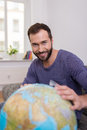 Happy successful man planning a summer vacation sitting in his living room with large world globe smiling happily at the camera Stock Images