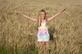Happy summer girl in wheat field a beautiful cute caucasian blond preteen with smiling facial expression stretching out her arms Stock Photography