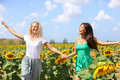 Happy summer girls laughing fun in sunflower field Royalty Free Stock Photos