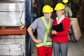 Happy supervisor showing clipboard to foreman young female at warehouse Stock Photos