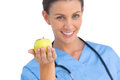 Happy surgeon holding an apple and smiling Royalty Free Stock Photo