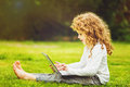Happy surprised child with laptop sitting on the grass. Royalty Free Stock Photo