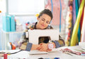 Happy tailor woman hugging sewing machine Royalty Free Stock Photo