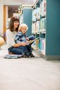 Happy teacher and boy reading book in library portrait of by bookshelf Royalty Free Stock Photography