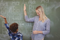 Happy teacher and schoolboy giving high five in classroom Royalty Free Stock Photo