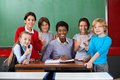 Happy teacher and schoolchildren portrait of african american female gesturing together at desk in classroom Royalty Free Stock Photos