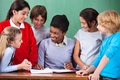 Happy teacher teaching young african american female children at desk in classroom Royalty Free Stock Images