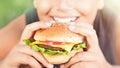 Happy teen boy eating burger Royalty Free Stock Photo
