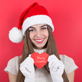 Happy teen girl with santa hat showing message merry christmas beautiful caucasian teenage smiling red paper heart red background Royalty Free Stock Images