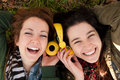 Happy teen girls sharing music two teenage lying on the grass headphones to listen to Royalty Free Stock Images