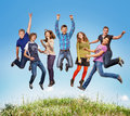 Happy teen jumpers group of teens jumping in the blue sky above the green grass Royalty Free Stock Image