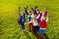Happy teen kids with lifted hands group of age school children standing on the lawn smile on faces lifting top view wearing warm Royalty Free Stock Image