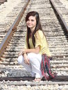 Happy teen long hair a teenage girl with dark and yellow blouse against a railroad tracks background Stock Image