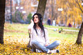 Happy teen woman listening to music and relax in autumn park. Yellow trees, beautiful fall time Royalty Free Stock Photo