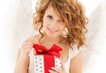Happy teenage angel girl with christmas gift holidays xmas and costumes concept Stock Photos