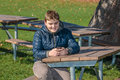 Happy teenage boy sitting relaxing in autumn park and sending text messages on cellphone young sunny warm day Royalty Free Stock Images