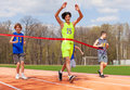 Happy teenage boy winning the race and coming first to finish red ribbon over group of sportsmen on stadium Royalty Free Stock Photos
