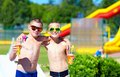 Happy teenage boys showing thumbs up in water park city aquapark Royalty Free Stock Photo